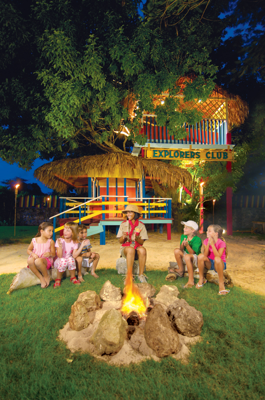 Children around a campfire, one of the many activities offered at the Explorer's Club for kids.