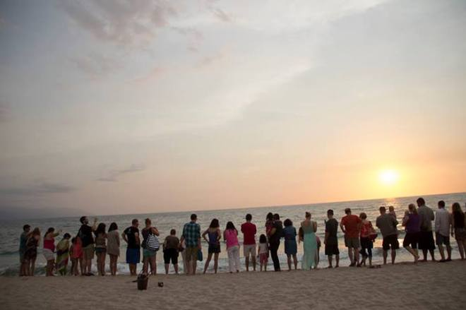 Our happy guests watch as the turtles swim off into the sunset.