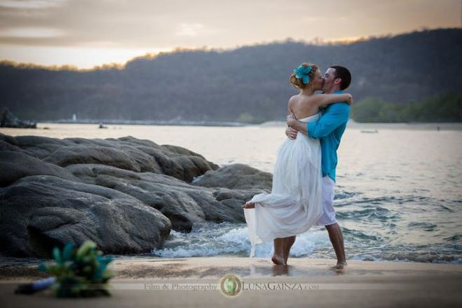 Miguel and his beautiful bride share a kiss on the shoreline at Dreams Huatulco Resort & Spa.