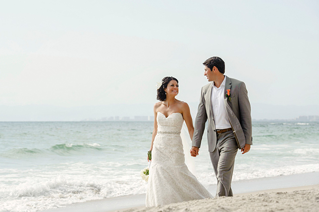 The newlyweds enjoy each other's company on a romantic beach stroll following the ceremony.