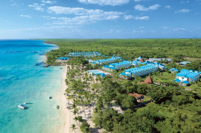 An aerial view of Dreams La Romana featuring the palm tree lined beach and the crystal-clear Caribbean.